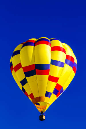 buoyant: Looking up at bright yellow, blue and red hot air balloon floating in early morning blue sky Stock Photo