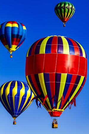 buoyant: Many brightly colored hot air balloons aloft in early morning blue sky