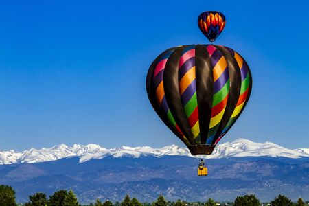 buoyant: Brightly colored hot air balloons aloft in early morning blue sky over snow covered mountains in the distance