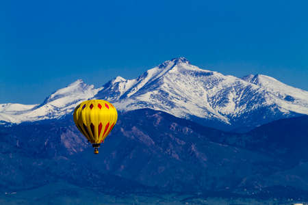 weightless: Bright yellow hot air balloon aloft in early morning blue sky over snow covered mountains in the distance