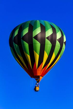 weightless: Green, yellow and red hot air balloon aloft in early morning blue sky Stock Photo