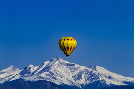 snow covered mountains: Bright yellow hot air balloon aloft in early morning blue sky over snow covered mountains in the distance