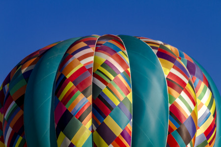 buoyant: Close up of brightly colored hot air balloon against early morning blue sky