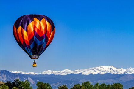 Felgekleurde luchtballon omhoog in de vroege ochtend blauwe hemel boven sneeuw bedekte bergen in de verte Stockfoto