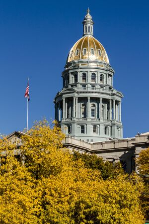 capital building: Close up of Colorado USA State Capitol Building dome in Denver, CO on sunny autumn morning with changing tree around building Stock Photo