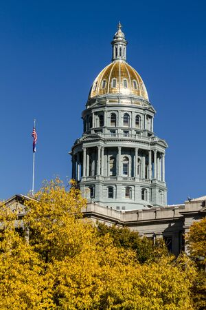 co: Close up of Colorado USA State Capitol Building dome in Denver, CO on sunny autumn morning with changing tree around building Stock Photo