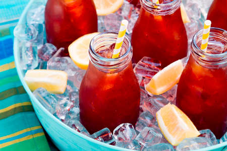 Close up of glass milk bottles filled with iced tea and fresh lemon with yellow swirled straw on ice in round blue metal tub sitting on bright blue wooden table with blue and green striped napkin