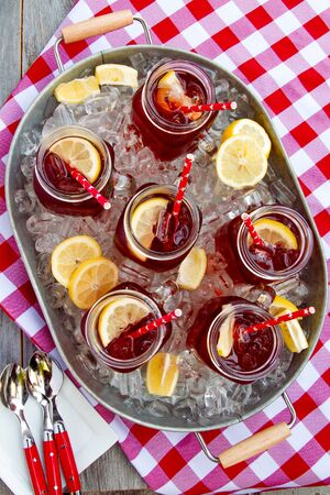 Mason jar mugs filled with iced tea and fresh lemon on ice in steel tub sitting on red gingham table cloth on wooden table from above Stock Photo