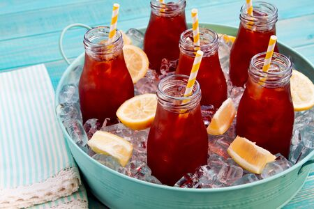 Glass milk bottles filled with iced tea and fresh lemon with yellow swirled straw on ice in round blue metal tub sitting on bright blue wooden table with blue and white striped napkin Stock Photo