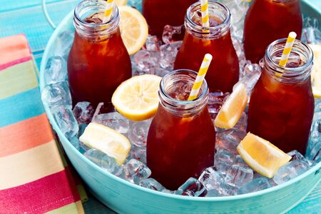 Close up of glass milk bottles filled with iced tea and fresh lemon with yellow swirled straw on ice in round blue metal tub sitting on bright blue wooden table with multi-colored striped napkin