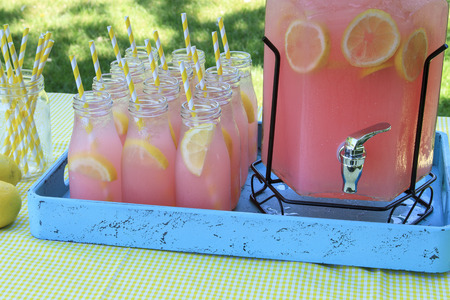 Close up of picnic party in the park drink table with large pitcher and glass bottles filled with ice cold pink lemonade and fresh lemons, with yellow swirled straws sitting on yellow gingham tablecloth