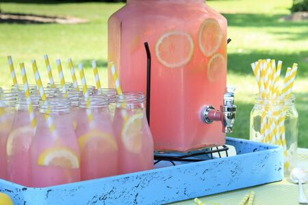 Close up of picnic party in the park drink table with large pitcher and glass bottles filled with ice cold pink lemonade and fresh lemons, with yellow swirled straws, spoons sitting on yellow gingham  tablecloth