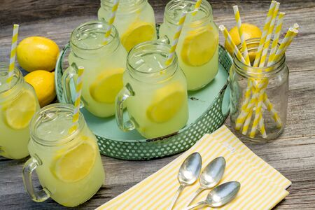 swirled: Mason jars filled with fresh lemonade with yellow swirled straws, spoons and striped napkin sitting on wooden table Stock Photo