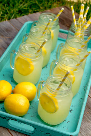 sour grass: Glass mugs filled with ice cold fresh lemonade and whole lemons sitting in drink tray on rustic wooden table Stock Photo