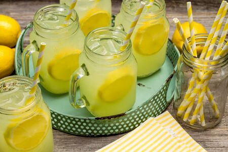 Picnic table with ice cold lemonade drinks with fresh lemons and swirled straws