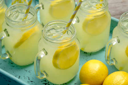 Close up of glass mason jars filled with ice cold lemonade and yellow swirled straws sitting in bright teal blue drink tray with whole lemons Stock Photo