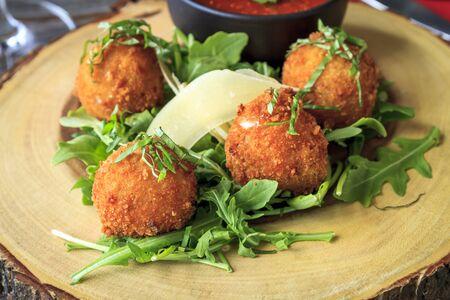 marinara sauce: Close up of fried risotto balls sitting on bed of micro green with parmesan cheese garnish and marinara sauce