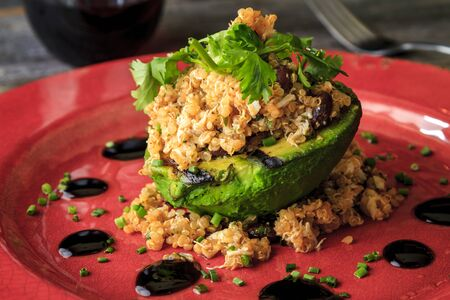 red quinoa: Grilled stuffed avocado appetizer with quinoa and crab meat garnished with olive oil and balsamic reduction and chives sitting on red rustic plate with glass of red wine and fork in background