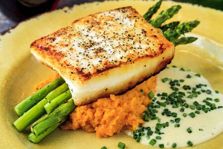 pureed: Close up of halibut filet with asparagus sitting on serving of pureed sweet potato and lemon butter sauce garnished with chives on rustic yellow plate with glass of red wine