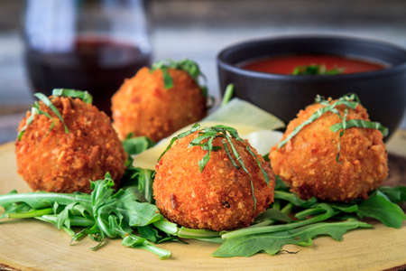 Close up of fried risotto balls sitting on bed of micro green with parmesan cheese garnish and marinara sauce for dipping with glass of wine on table