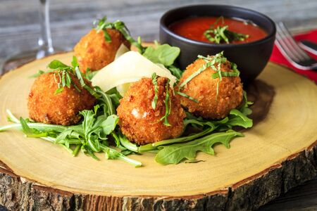 Rustic wooden plate with fried risotto balls sitting on bed of micro green with parmesan cheese garnish and marinara sauce for dipping Stock Photo
