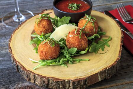 marinara sauce: Fried risotto balls sitting on bed of micro green with parmesan cheese garnish and marinara sauce for dipping on rustic wooden table