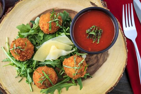 marinara sauce: Close up of fried risotto balls sitting on bed of micro green with parmesan cheese garnish and marinara sauce for dipping with fork and knife shot from above