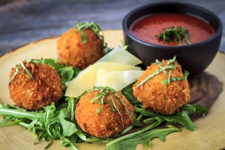 marinara sauce: Close up of fried risotto balls appetizer sitting on bed of micro green with parmesan cheese garnish and marinara sauce for dipping