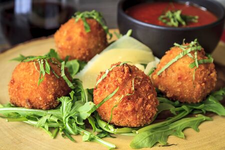 Close up of fried risotto balls sitting on bed of micro green with parmesan cheese garnish and marinara sauce and glass of wine Stock Photo