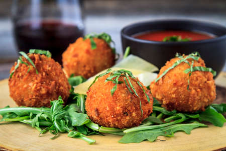 marinara sauce: Close up of fried risotto balls appetizer sitting on bed of micro green with parmesan cheese garnish and marinara sauce for dipping with glass of wine on table
