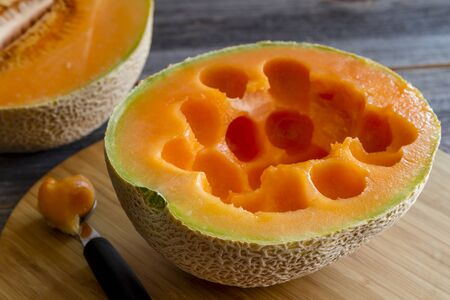 Close up of two cantaloupe melon halves with melon baller tool on round cutting board