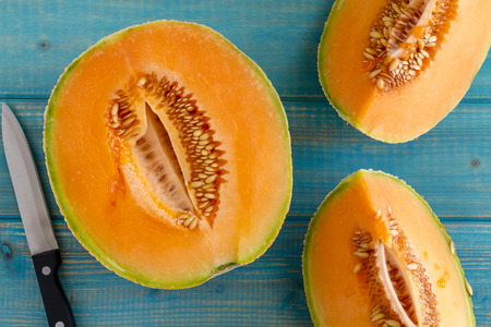 Open half of cantaloupe melon  and two quarters sitting on bright blue wooden with knife