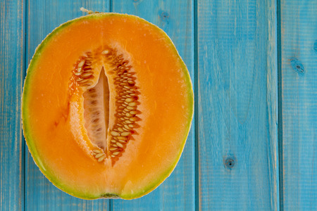 Open half of cantaloupe melon sitting on bright blue wooden table Standard-Bild