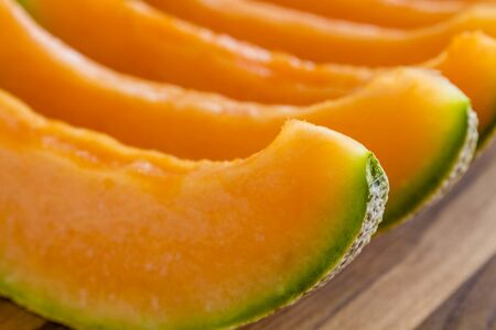 Close up of cantaloupe melon slices sitting in row on wooden cutting board Stock Photo