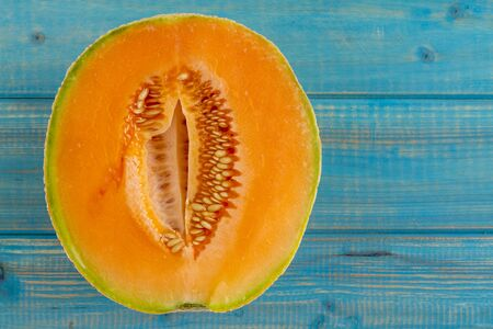 Cut open half of cantaloupe melon sitting on bright blue wooden tabletop Standard-Bild
