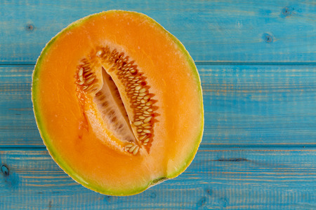 Open half of cantaloupe melon sitting on bright blue wooden at an angle