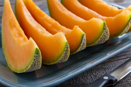 Cantaloupe melon slices sitting on blue platter in a row with knife in foreground