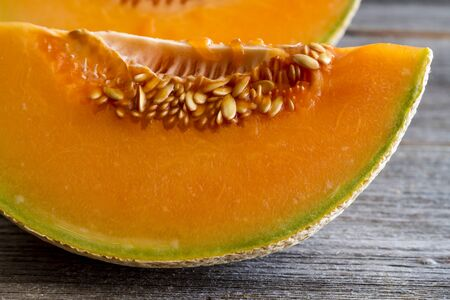 at close quarters: Close up of two cantaloupe melon quarters with seeds in row sitting on rustic wooden table top