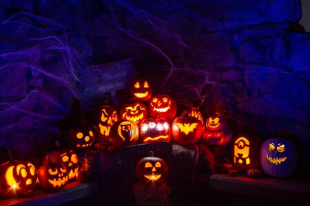 Display of candle lit carved Halloween pumpkins in stone room with spider webs and eerie signs lit with blue and red light Imagens