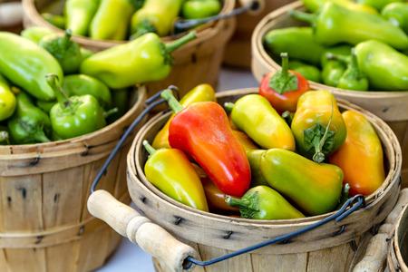 bushel: Brown bushel baskets filled with farm fresh hot pepper varieties sitting on table for sale at farmers market