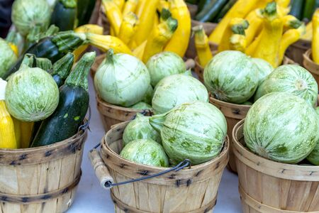 bushel: Farmers market display with brown bushel baskets filled with farm fresh yellow and green zucchini, calabacita and patty pan squash