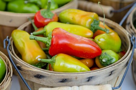 bushel: Close up of brown bushel basket filled with farm fresh multi-colored hot pepper varieties sitting on table for sale at farmers market