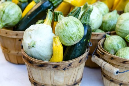 bushel: Brown bushel baskets filled with farm fresh yellow and green zucchini, calabacita and patty pan squash sitting on table for sale at farmers market