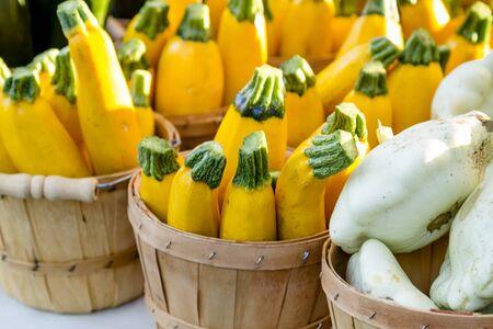 bushel: Yellow zucchini in brown bushel baskets sitting on table at farmers market