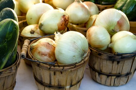 bushel: Brown bushel baskets filled with farm fresh spanish onions sitting on table for sale at farmers market