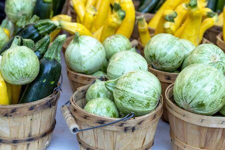 bushel: Close up of farmers market display with brown bushel baskets filled with farm fresh yellow and green zucchini, calabacita and patty pan squash