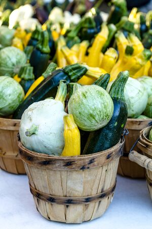 bushel: Table at farmers market with brown bushel baskets filled with farm fresh yellow and green zucchini, calabacita and patty pan squash