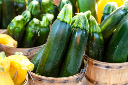 Fresh the farm zucchini in brown bushel baskets sitting on table at farmers market Stock Photo