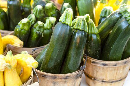 bushel: Home grown zucchini in brown bushel baskets sitting on table at farmers market