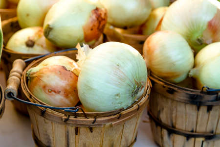 bushel: Home grown yellow onions in brown bushel baskets for sale at farmers market